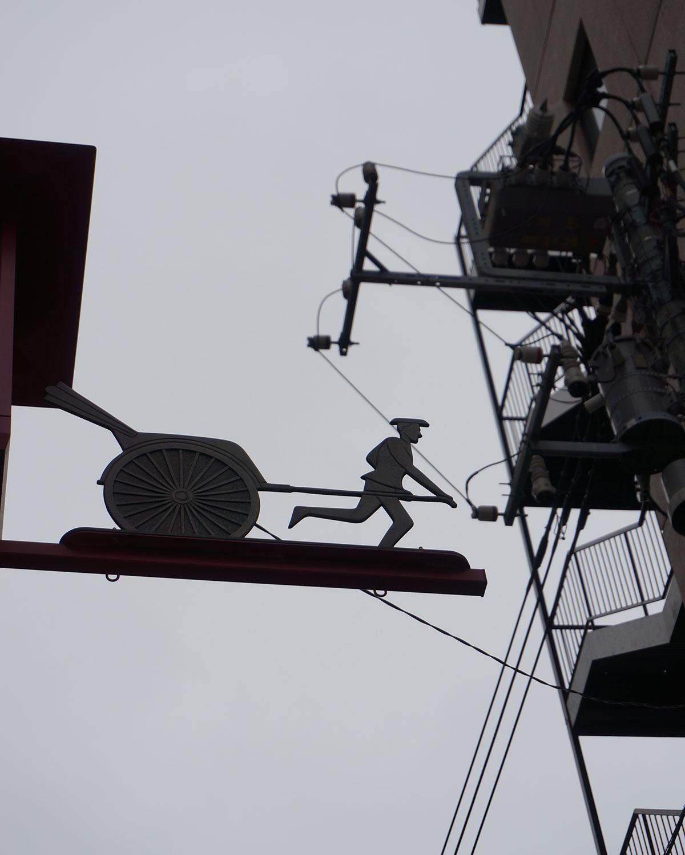 車力門通りの名前の由来は、松平摂津守の上屋敷があった頃、物資が荷車で運び込まれた道だったことから。入り口のゲートの上には車力のオブジェが。
