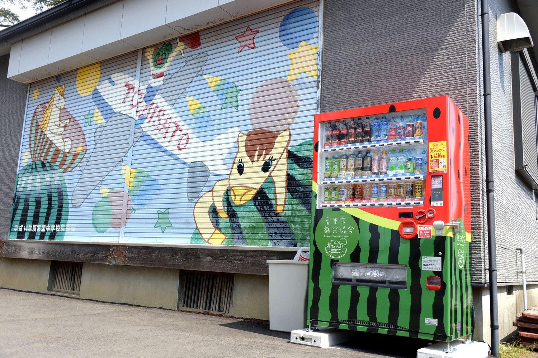 境内の公民館横に置かれたスイカ柄の自販機と中学生のスイカ画。