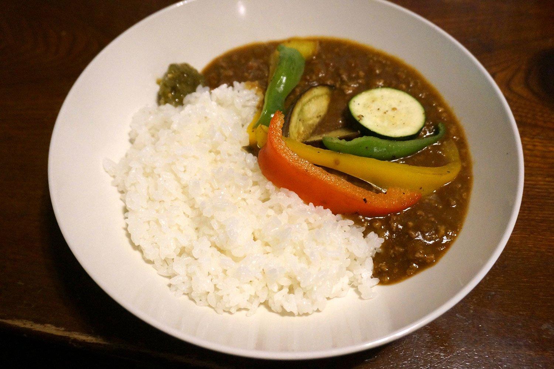お店は料理メニューも複数あり、カレーも名物。写真は現在提供中の夏野菜のカレー900円。食事はすべてミニサラダ・ミニスープ・コーヒーまたは紅茶付き。