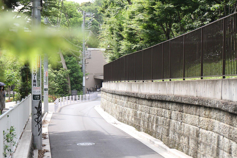 かつて、坂の上で石臼の目を切る仕事をしていた人がいたことから、その名がついたとされる目切坂。この先に東京音楽大学。