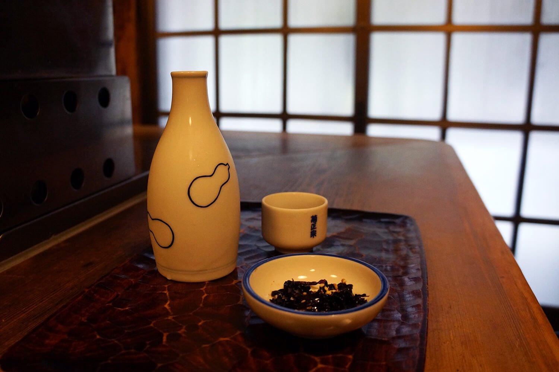 お通しの昆布の佃煮とともにお盆に。これがカウンター席の基本スタイル。菊正宗樽酒は一合700円。