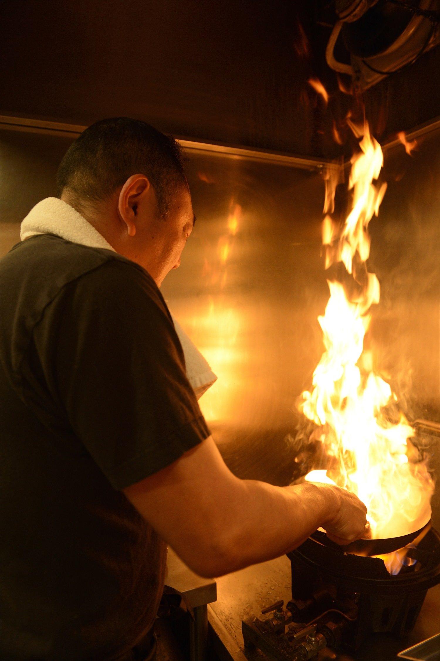 火柱を上げて鍋をあおる伊藤さん。