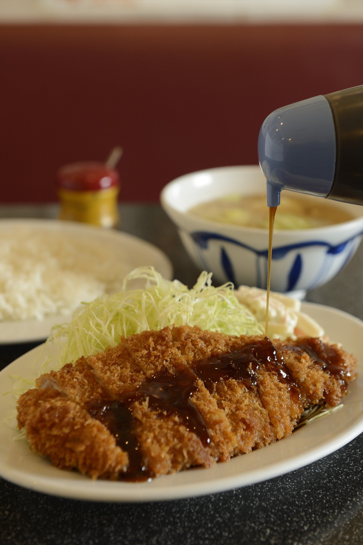 ロースとんかつ定食は驚愕の600円!キャベツを直前に投入して甘みと食感を醸す豚汁付きだ。とんかつのお持ち帰り率も高い。