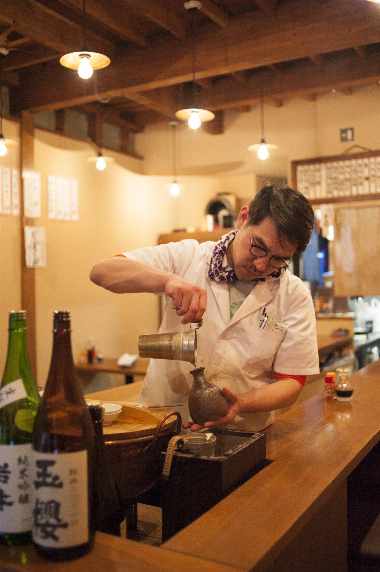 同店は吉祥寺の燗酒専門店「カイ燗」の2号店。酒を注ぐのが店主の小倉拓也さん。