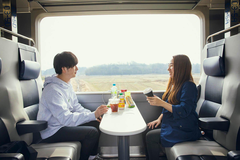 大きな車窓に各席テーブルが設置されているのがうれしい。乗車前に食べ物や飲み物を買おう。席に電源も付いているので移動中に充電も。