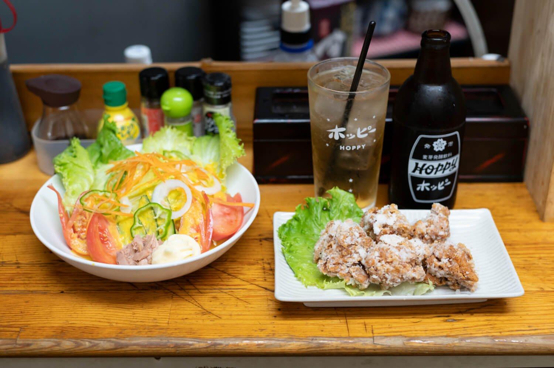ラーメンの麺が潜む区民サラダ500円、ホッピー390円など。