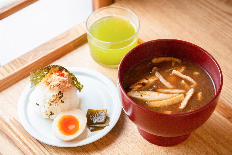 きのこと油揚げ、焼きネギの味噌汁とスパイシーツナおにぎりのセット600円。煮卵とお茶付き。