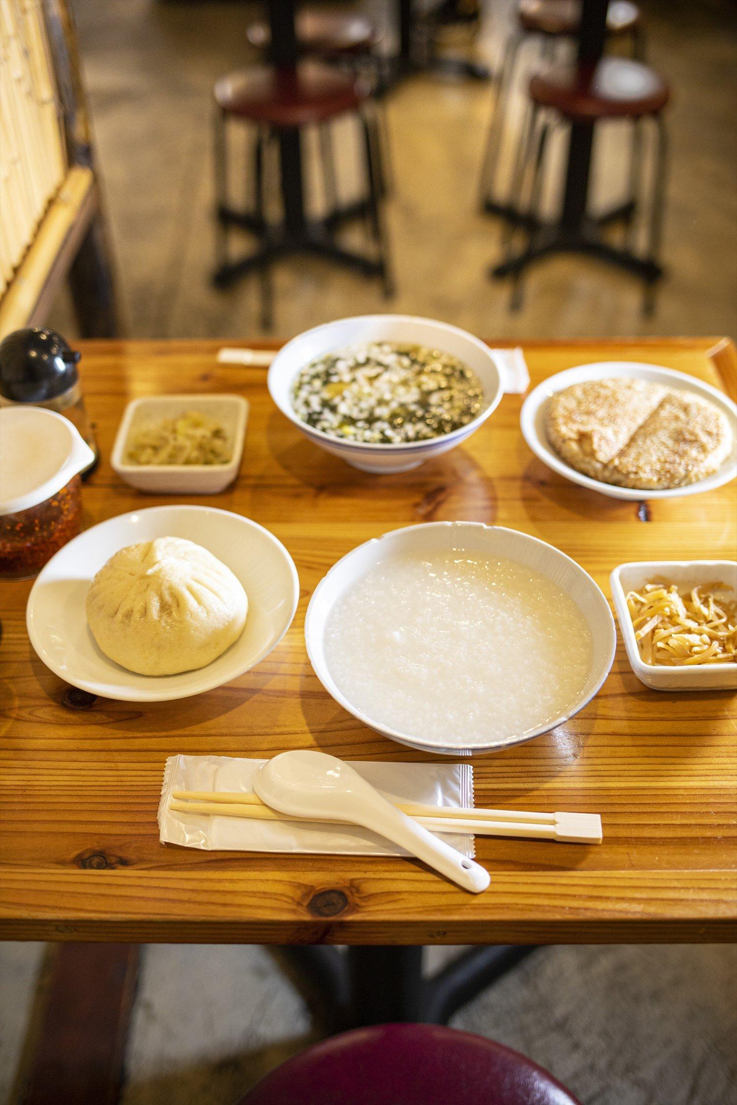 手前から肉まんと白粥セット、焼き餅と海苔雲呑スープセット。各日替わり漬物付き500円。
