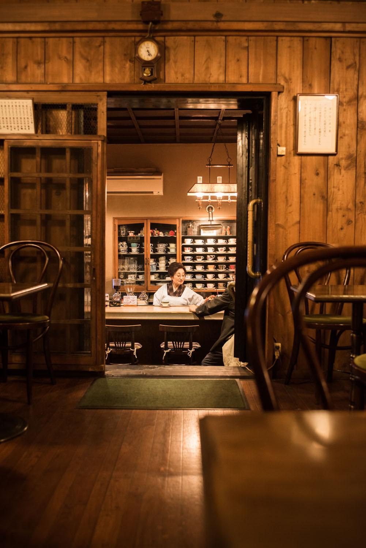 蔵の奥にあるテーブル席は、建物の重厚感も、カウンターの景色も両方楽しめる特等席。蔵の入り口には、金網の格子引き戸が当時のまま。