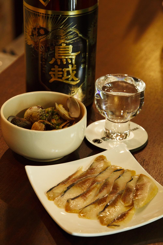 あさりの酒蒸400円。アテは皿に盛り、ツマミによっては温めて提供。酒は120mlで300~500円。