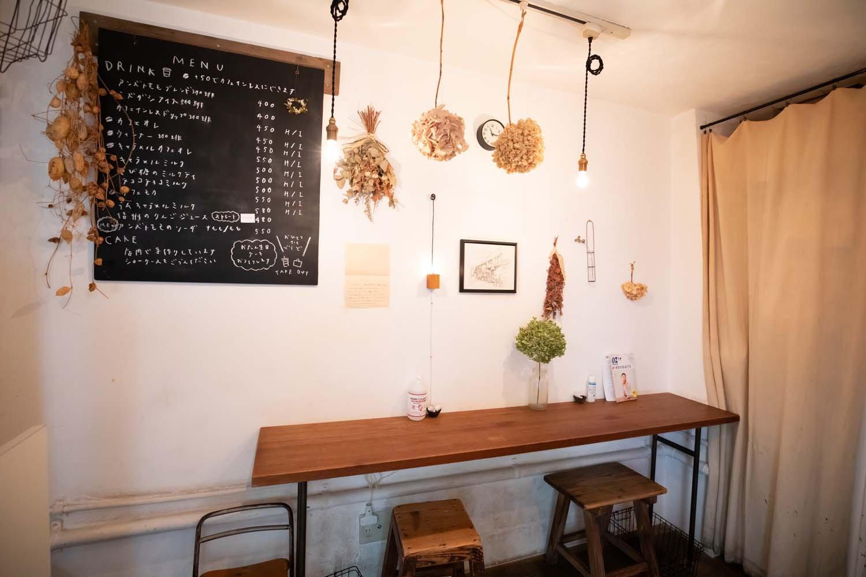壁際のカウンター席。白壁を暖色の電球が照らす