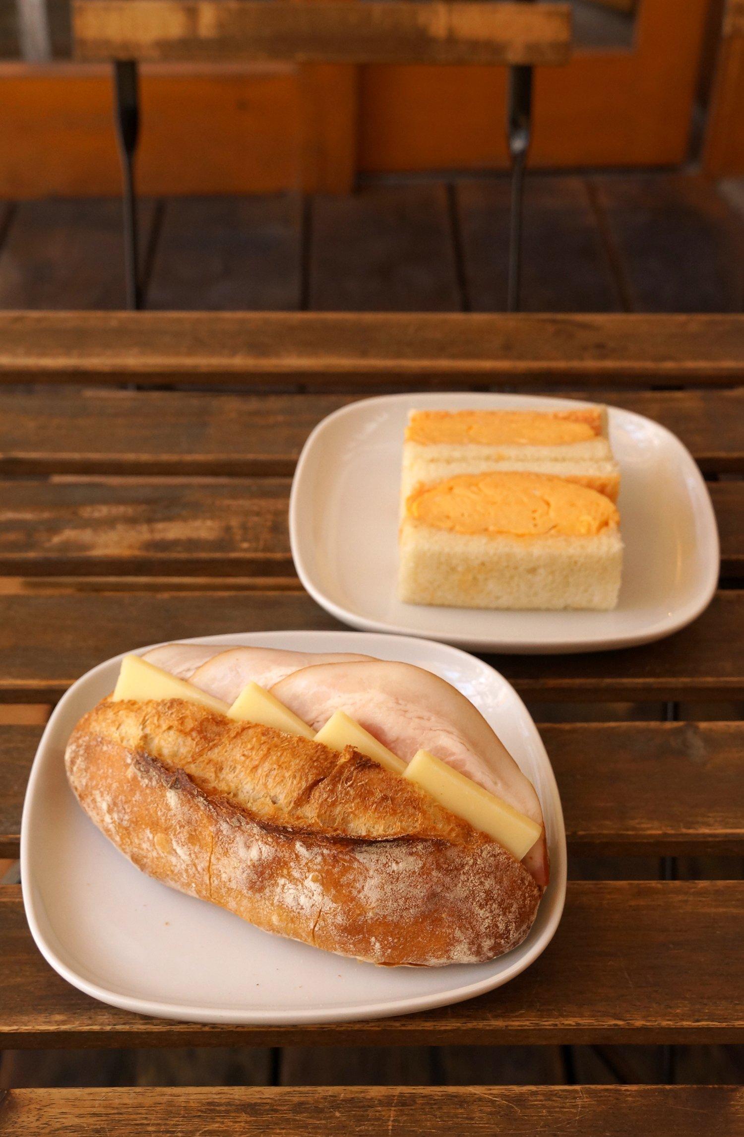 手前はハムとチーズのバゲットサンド480円、奥は厚焼きの卵焼きを挟んだオムレツサンド350円。
