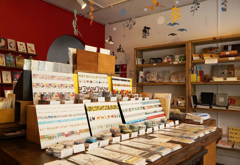 店内は壁面やテーブルの上だけでなく、天井からも紙モノ雑貨でいっぱい。