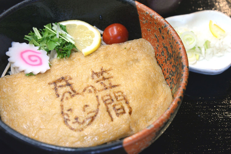 大きな油揚げが麺を覆う「稲荷そば」。お狐さんの顔もキュート。