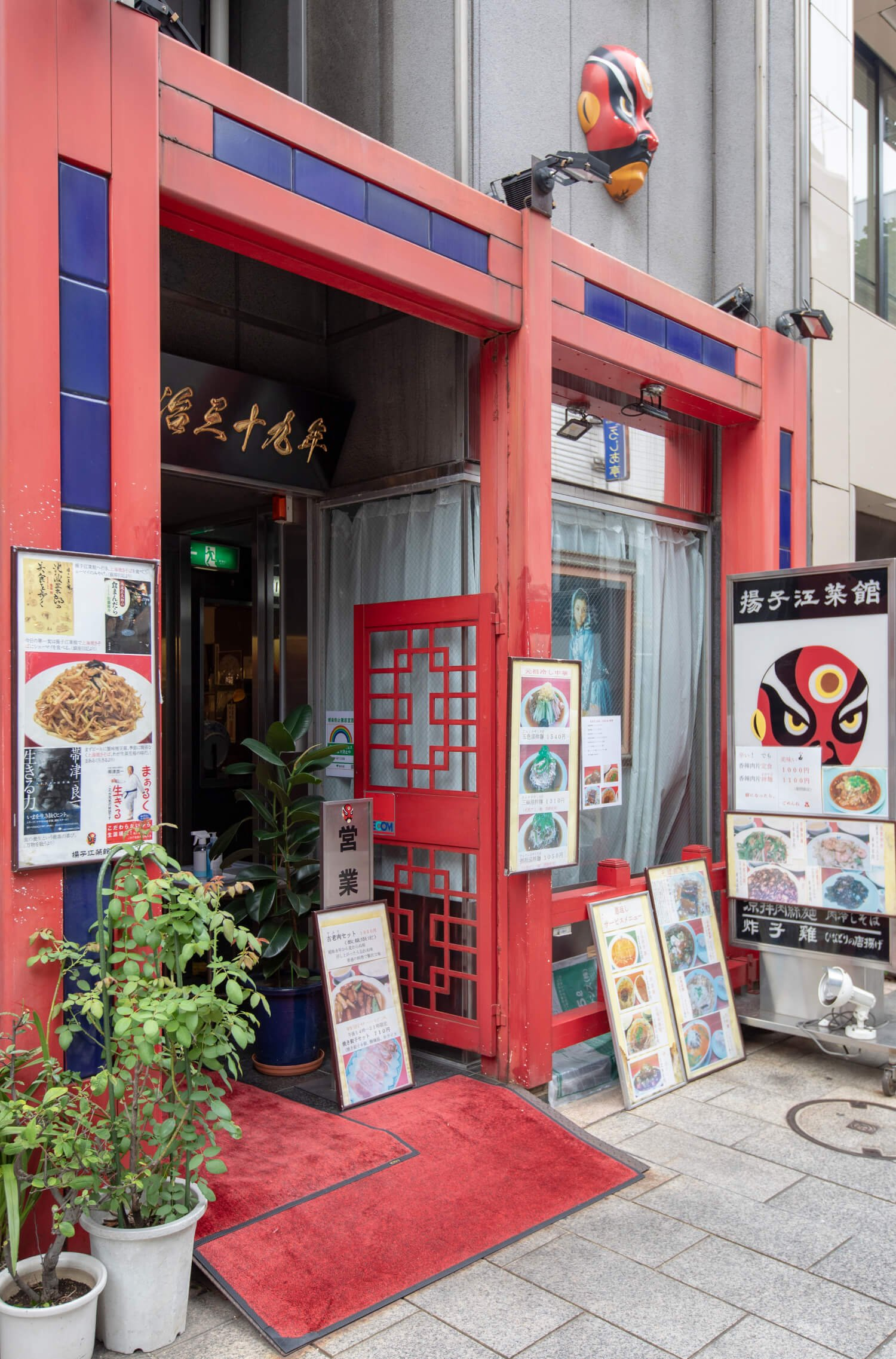 赤色が目を引く入り口。店のシンボルである京劇のお面があちこちに。