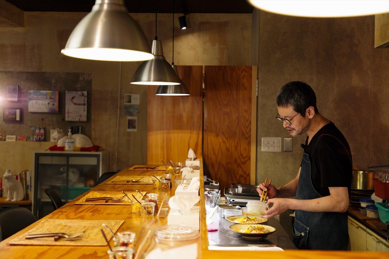 全7席のカウンターで野菜を盛る滝沢さん。「カレーのこと以外は内装も道具も結構行き当たりばったりです(笑)」。
