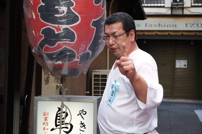 頂点からさらなる高みを目指す男、店主の伊與田さん。自ら「危険人物」のバッジを付ける。