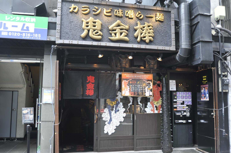 黒の看板に黄金の店名が光り輝く。店頭にある金棒や鬼の面も印象的。