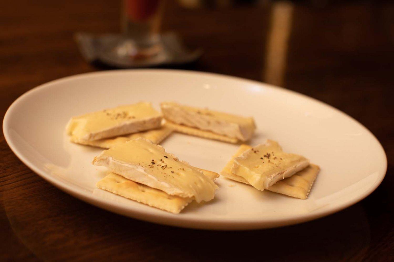 お通しのひとつ。カマンベールチーズが乗ったクラッカー。