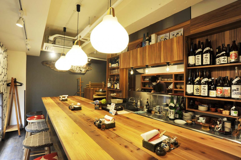 大きな白木のテーブルが置かれた店内は、小粋な料理屋といった雰囲気。棚には神奈川の地酒が並ぶ。