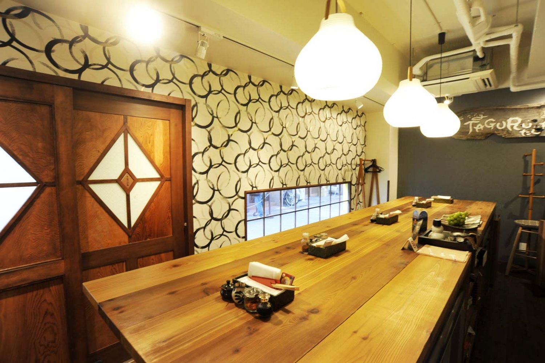 大きな白木のテーブルが置かれた店内は、小粋な料理屋といった雰囲気。棚に神奈川県産の地酒が並ぶ。