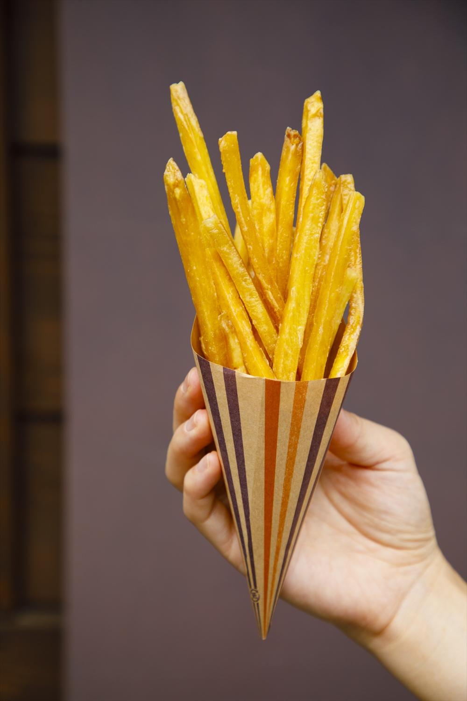 食べ歩き用 揚げたて芋けんぴ300円/揚げたてゆえ包みを持つ手に温もりを感じる。元々のサツマイモのサイズが大きいので、1本が長い。腹持ちも◎。