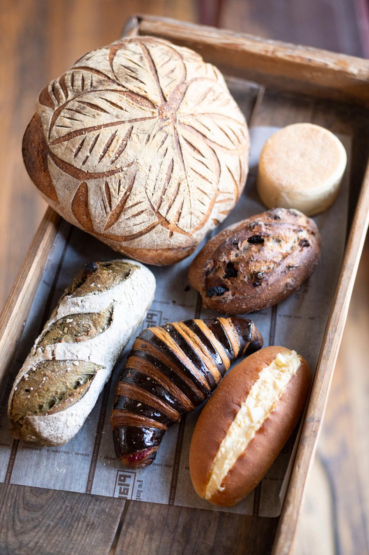 左上から時計回りに、はなまんてん100田舎パン1296円、ハナマンテン100イングリッシュマフィン183円、いちじくとナッツのライ麦パン345円、たっぷりたまごサンド280円、しましまフランボワーズクロワッサン302円、河越抹茶とホワイトチョコくるみの入ったフランスパン453円。 大きな田舎パンはトーストがおすすめ。たっぷりたまごサンドは噛みしめがいのあるコッペパン。