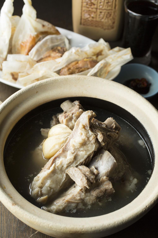 スペアリブを漢方入り出汁で煮込む肉骨茶(バクテ) 2090円(2人前)と、紙に包み揚げるペッパーチキン(2p)700円。