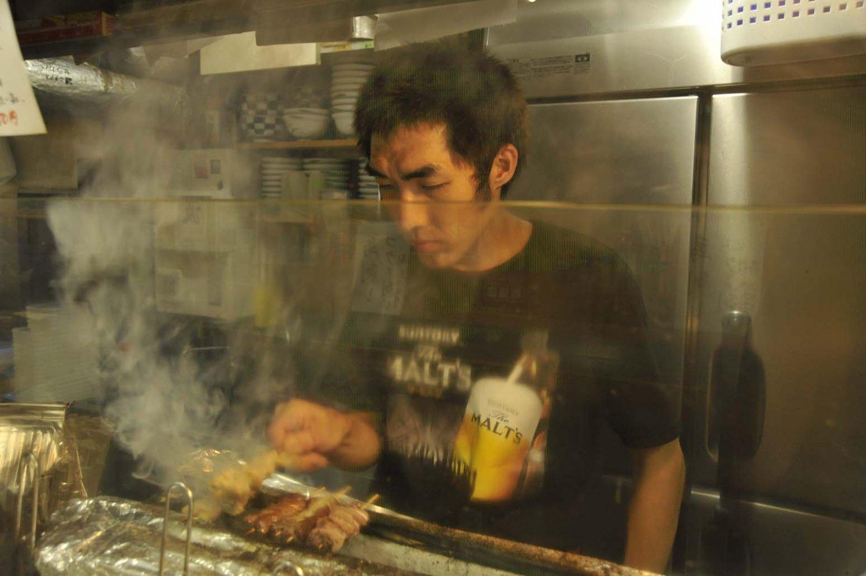 モクモクとした煙の中でもつを焼く店長の小原涼さん。