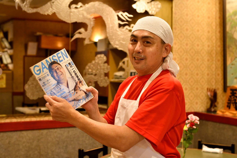 3代目松田将吾さんが手にしているのは、この店の同人誌『GANSEN』だ。2000部発行されコミックマーケットで販売されたという。雁川ファンによる完全な手作り。丸一冊ファンブックが作られる町中華なんて聞いたことがない、第2号もぜひ見たいです!