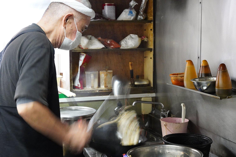 流れるような動きで炒飯を作る店主の亀山勉さん。鍋を振る音がリズミカルに響く。