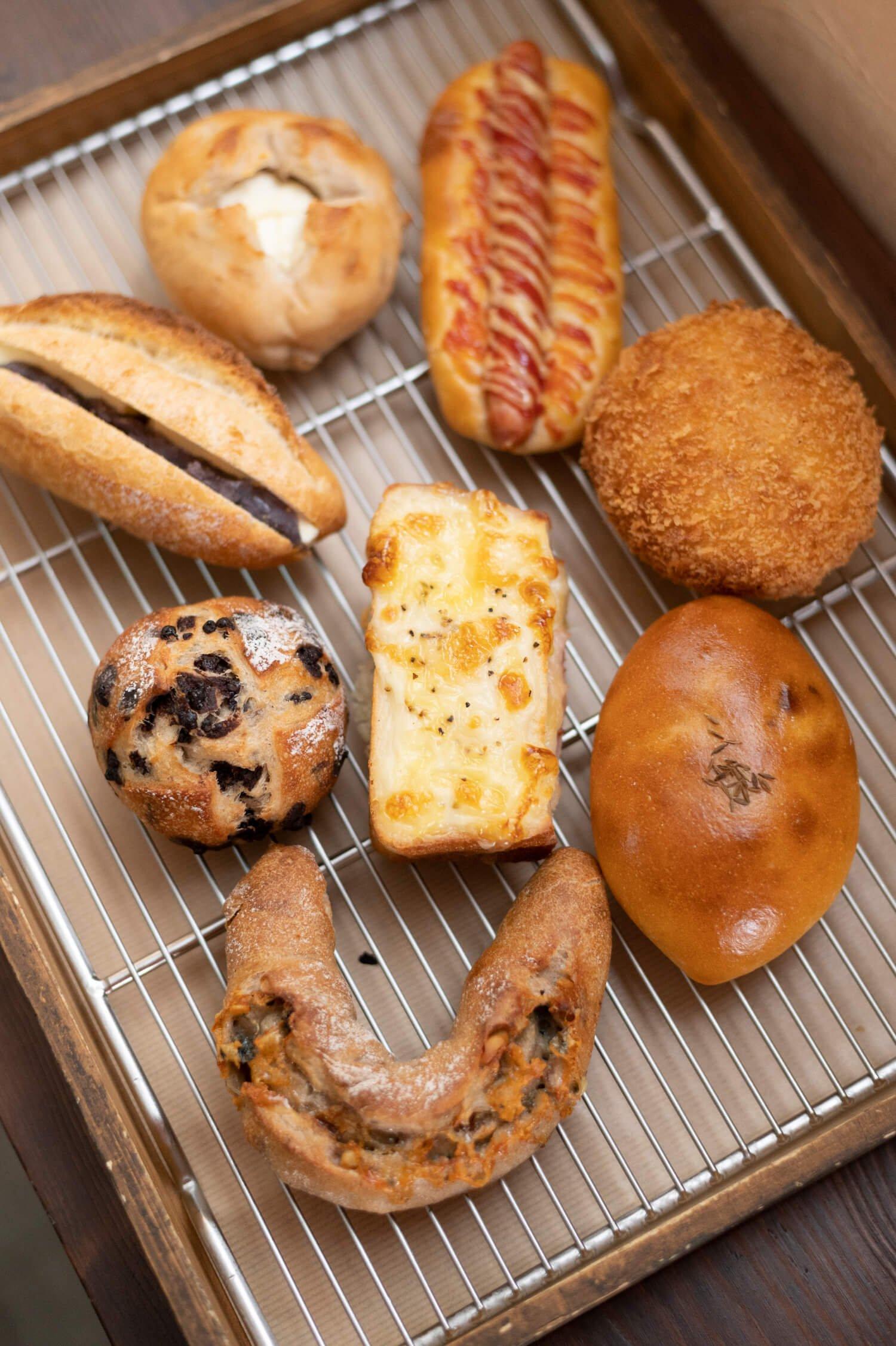 真ん中はMAGU食パンのクロックムッシュ226円。右上から時計回りに、ウインナーパン216円、カレーパン216円、チキンマサラの包み焼き216円、ゴルゴンゾーラハニー248円、チョコチップフランス194円、あんバター248円、クルミとクリームチーズ226円。 中央のクロックムッシュは、ゆめちからで作った食パンを使用。