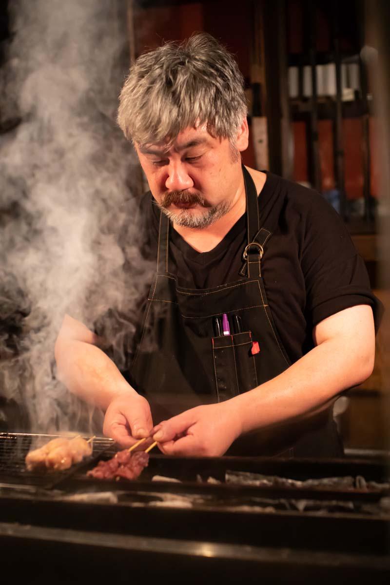 店主の安達英一郎さん。串ごとに味付けを変えて、火力強めの備長炭で焼き上げる。