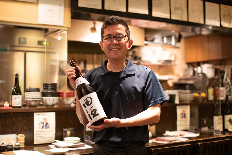 店主の黒田英徳さんは北赤羽出身。手に持っているのは田酒。おすすめの一本だ。