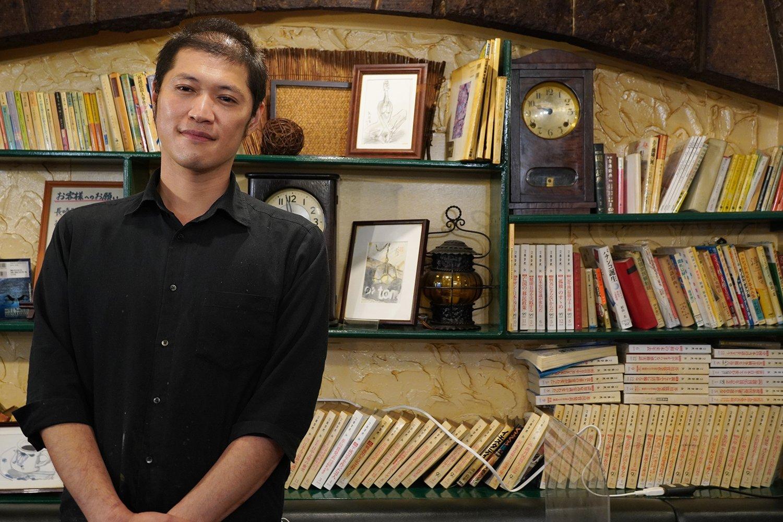 店長の芦澤さん。後ろの本は「友路有図書館」の蔵書で貸し出しが可能。