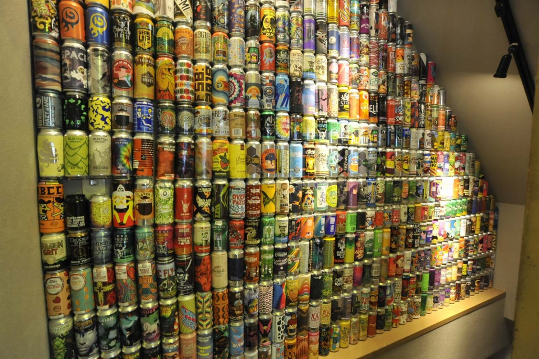 2階へと続く階段の壁には、クラフトビールの空き缶がずらり!