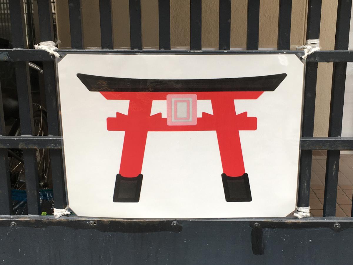 駐車場に掲げられた鳥居の絵。これだけで全てを理解してもらえるだろうか(田端)