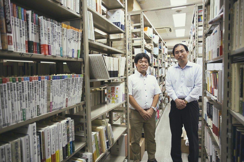 出版社ごとに新刊が並ぶ。お話を聞いた川瀬哲史さん(右)と小谷野哲矢さん。