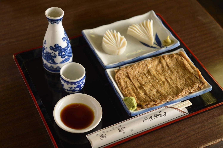 日本酒は「白雪」500円。肴には、そばつゆで煮た油揚げ甘辛煮350円や厚切りの板わさ500円がピッタリ。