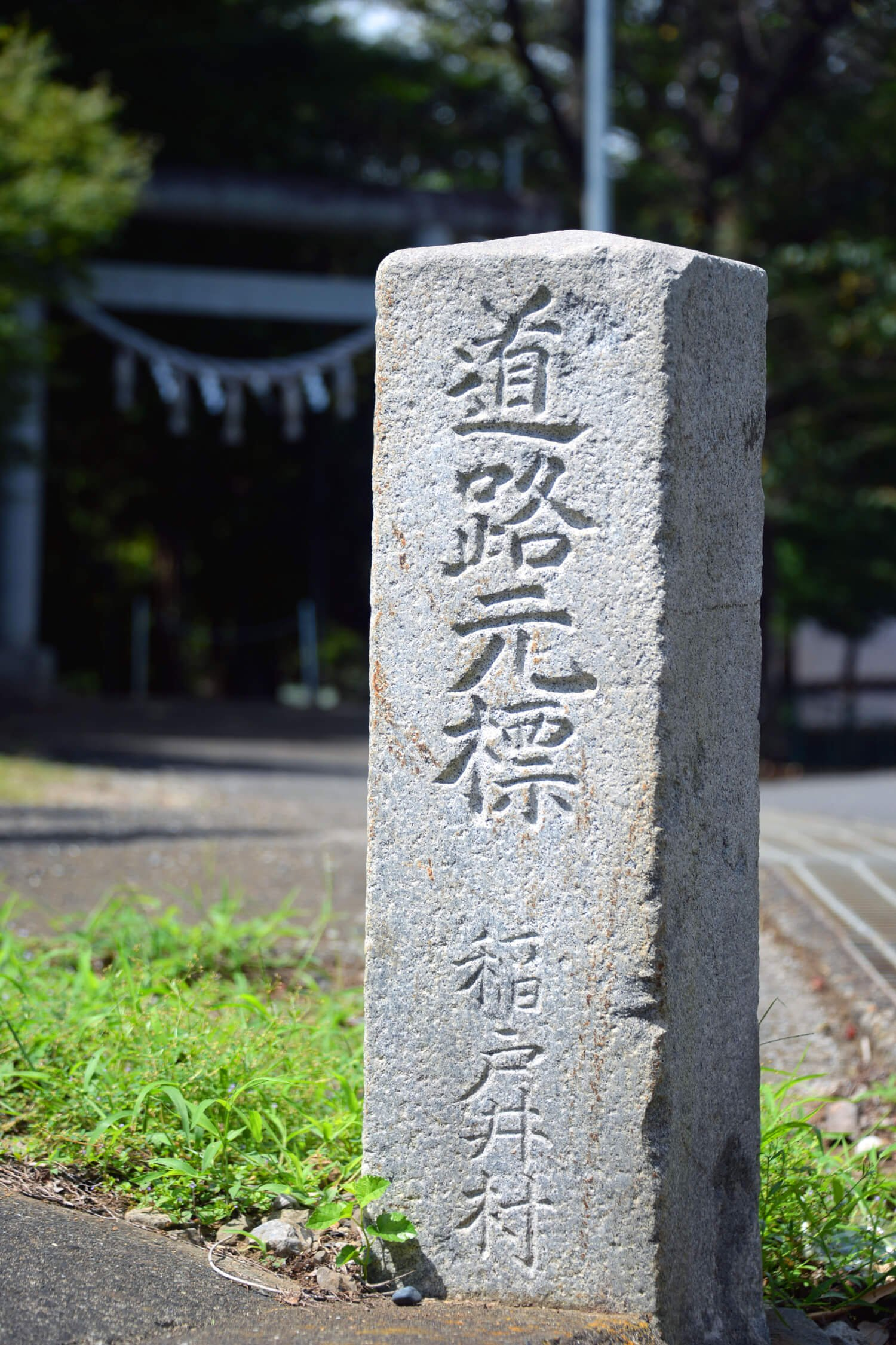 下部に村名が刻まれた、変わったデザインの道路元標。役場跡に立つ。