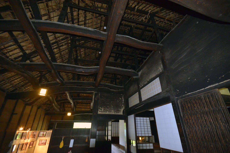 土間の天井の梁組み。三段に組み上げた梁丸太と大黒柱が見える。