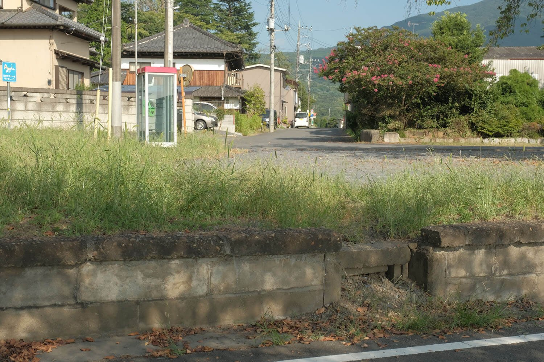 サイクリングロードからホーム越しに見る駅前。ホーム欠き取り部分は職員用の昇降箇所かと思う。駅前は閑静な住宅地である。