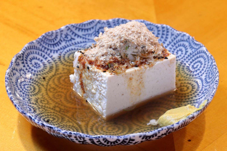 豆腐は木綿豆腐で半丁分の大きさ。仕上げに少量の醤油をかける。