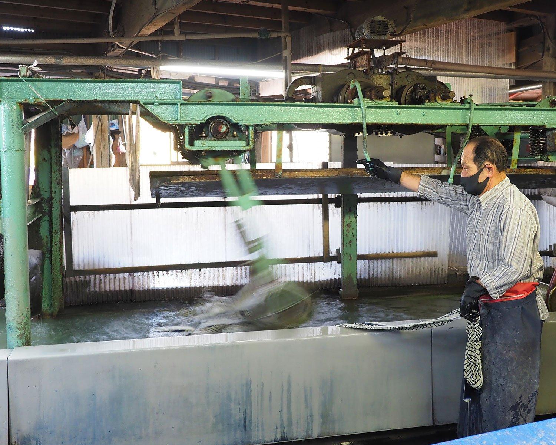 機械が力強く反物を洗って送り出す。水が冷たく、濡れた反物は重いため、冬はかなりの重労働だ。
