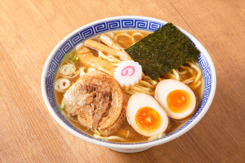 ジャパン+燻製味玉 980円。チャーシューは豚骨スープで3時間、タレで一晩、取り出して2日間寝かせて熟成する。「店名にちなみ、なにかいぶさないとなあ」と考えた東野さんは、味玉を燻製にした。