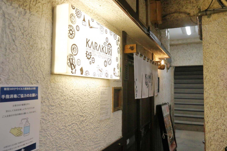階段を下りると暖簾(のれん)を下げた玄関と歯車を描いた看板が見える。