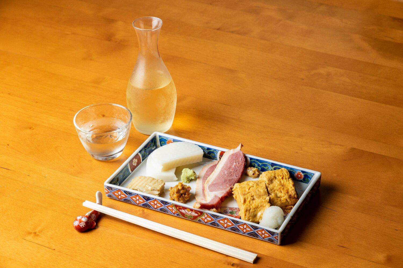 出汁巻き、味噌豆腐、鴨スモークなどのおつまみ盛り合わせ800円。酒は石川の菊姫650円。