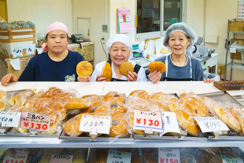 佐藤さん一家が手にしているのは、右から、牛すじ黒カレー150円、特製カレーパン、辛口カレー130円、角切り野菜のカレーパン130円。