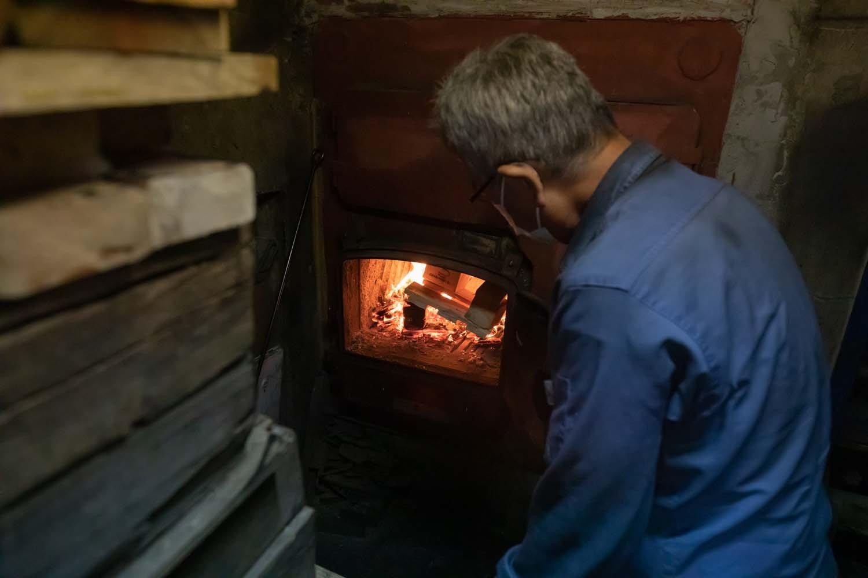 裏のボイラー室で釜に薪をくべる松柳さん。職人技だ。