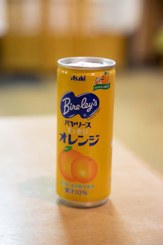小学生以下の子供にサービスしているジュース缶。